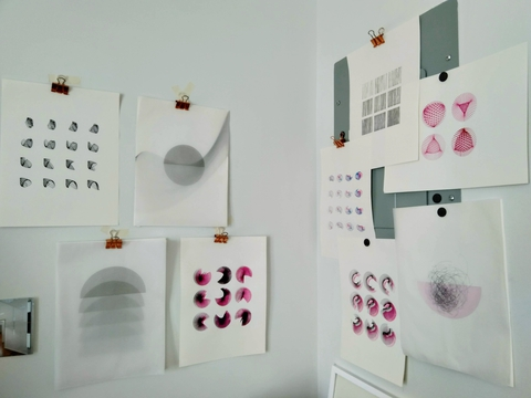 photo of various plotter drawings hung on wall